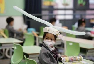 У Китаї діти повернулися до шкіл і носять противірусні капелюхи